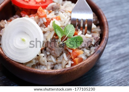 Wooden bowl full of freshness pilaw near fork on the table - stock photo