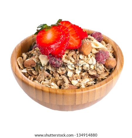 Wooden bowl full of healthy fruit and nut muesli with fresh strawberry on top - stock photo