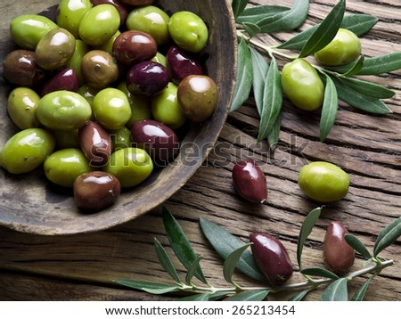 Wooden bowl full of olives and olive twigs besides it. - stock photo