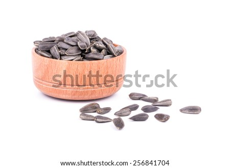 Wooden bowl full of seeds and grains scattered - stock photo