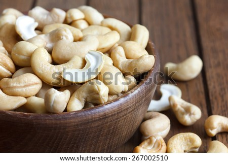 Wooden bowl of cashew nuts from above. On dark wood. - stock photo