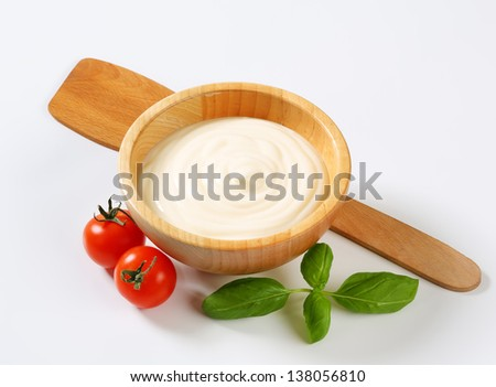 wooden bowl of cream with tomatoes and basil leaves - stock photo