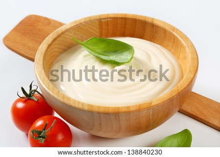 wooden bowl of creamy mayonnaise with basil and tomatoes - stock photo