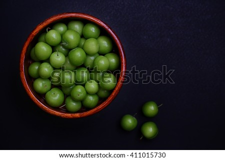 Wooden bowl of green plums. Food, healthy eating and lifestyle concept - stock photo
