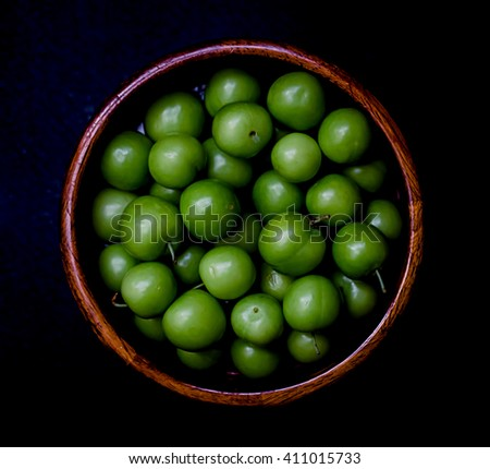 Wooden bowl of green plums. Food, healthy eating and lifestyle concept