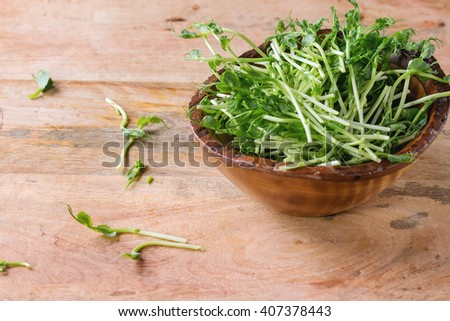 Wooden Bowl of pea sprouts over textured wooden background.