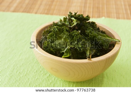 Wooden bowl of roasted kale chips - stock photo