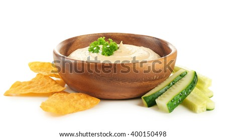 Wooden bowl of tasty hummus with chips, parsley and cucumber, isolated on white
