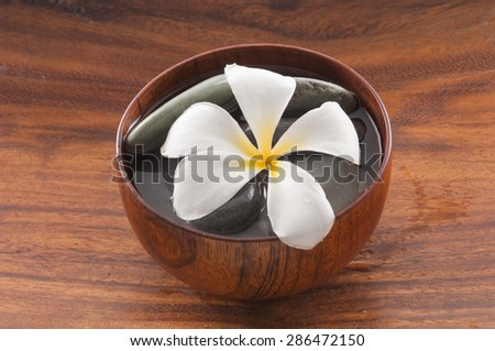 Wooden bowl of white frangipani and stones - stock photo