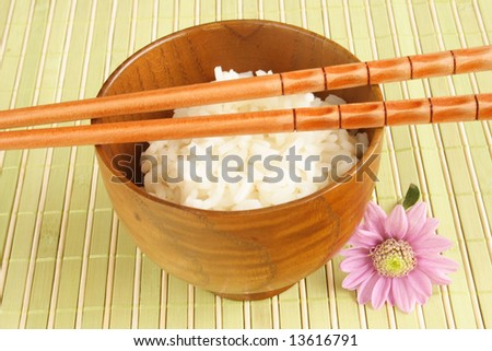 Wooden bowl of white rice and chopsticks - stock photo