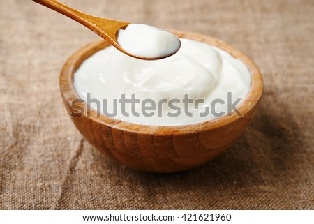 wooden bowl of white yoghurt and spoon - stock photo