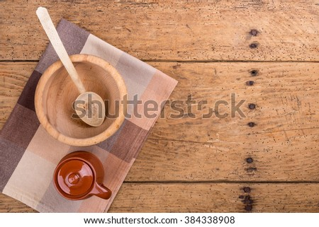 Wooden bowl, spoon and tablecloth on an old rustic wooden table - copy space - stock photo