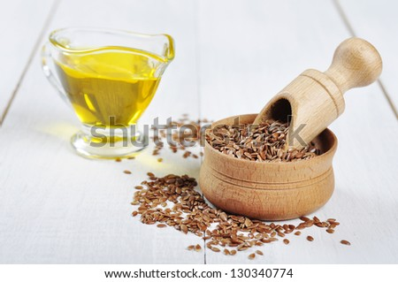Wooden Bowl with brown flax seed and linseed oil over white wooden background - stock photo