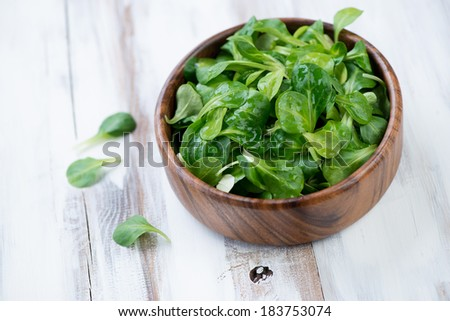Wooden bowl with corn salad leaves, horizontal shot - stock photo