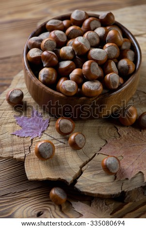 Wooden bowl with hazelnuts, selective focus, studio shot