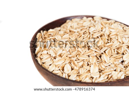 Wooden bowl with oats flakes pile on white background.