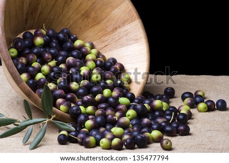 wooden bowl with olives over burlap background - stock photo