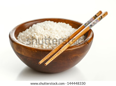 Wooden bowl with rice and Chinese chopsticks - stock photo