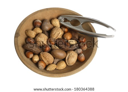 Wooden bowl with various nuts and a nutcracker on white background - stock photo