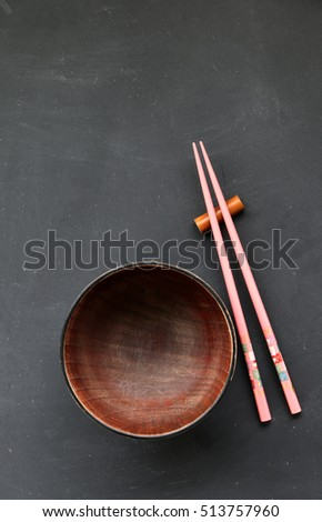 wooden bowls and wooden chopsticks on the blackboard. Flat lay.