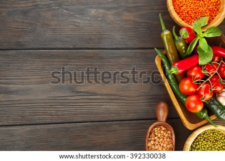 Wooden bowls of various lentils with red and green hot chilli peppers with leaves and tomatoes on a wooden background - stock photo