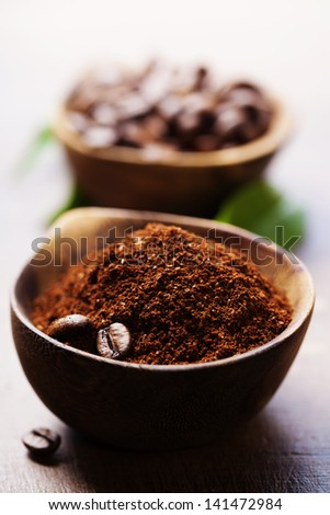 Wooden Bowls with coffee beans and ground coffee - stock photo