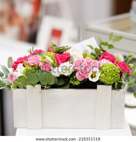 Wooden box as vase with flowers - stock photo