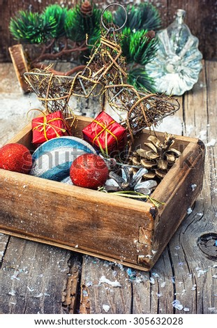 Wooden box full of Christmas toys and cones on wooden background.Selective focus - stock photo