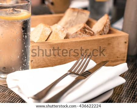 Wooden Box of Fresh Bread and Glasses of Water with Lemon SLices and Other Drinks on a Table in a Restaurant