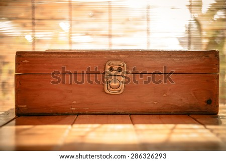Wooden box resting on a wooden table. vintage style.
