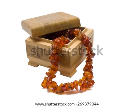 Wooden box with amber necklace isolated on white  - stock photo