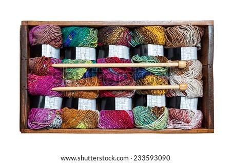 Wooden box with colorful yarn - stock photo