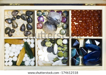 Wooden box with different gemstones - stock photo