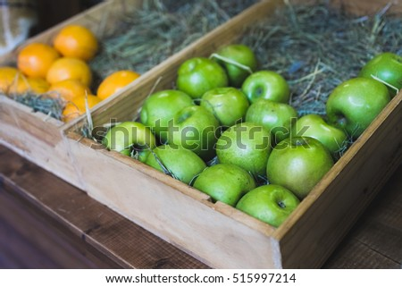 Wooden box with fresh green apples on display in a fruit shop