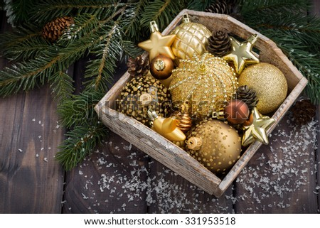 wooden box with golden Christmas decorations on table, top view, closeup - stock photo