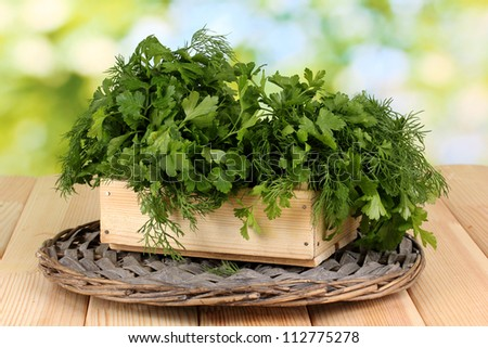 Wooden box with parsley and dill on wicker cradle on wooden table on natural background - stock photo