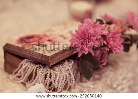 Wooden box with pearls and flower on a wedding table  - stock photo