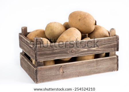 Wooden box with potatoes - stock photo