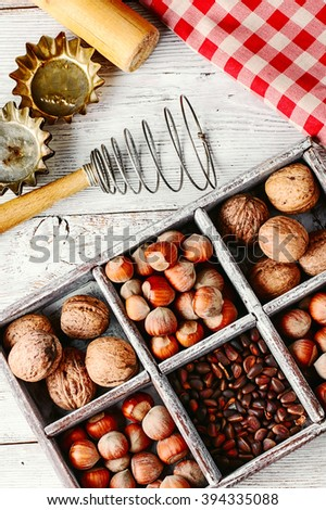 Wooden box with walnuts and pine nuts and hazelnuts - stock photo