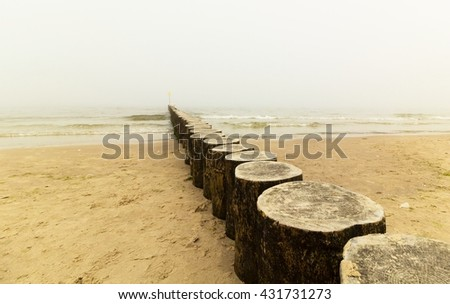 Wooden breakwater, beach and sea in the fog