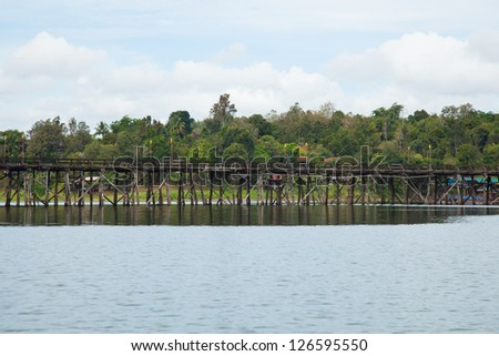 Wooden bridge across the river. The mountain in the back and on both sides of the river. - stock photo