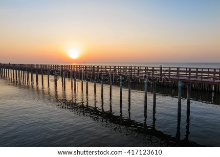 Wooden bridge and bamboo wave breaker in the sea at Sunrise
