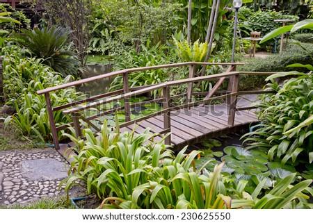wooden bridge in a beautiful garden. - stock photo