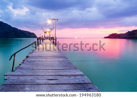 Wooden bridge in the port over sea between sunset