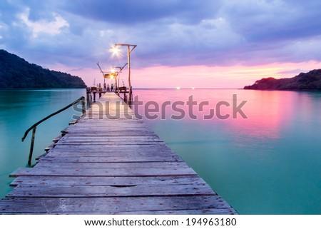 Wooden bridge in the port over sea between sunset - stock photo