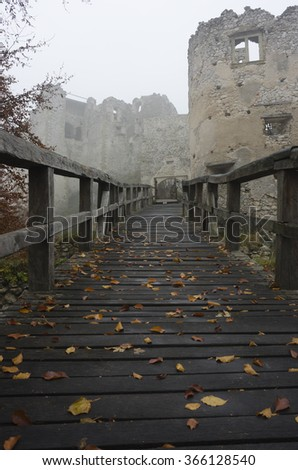 wooden bridge leading to an old mystical castle ruin in fog,mist - stock photo