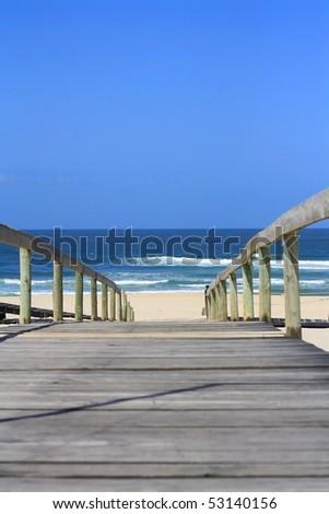 wooden bridge leading to the sandy shore - stock photo