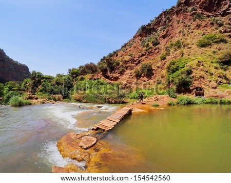Wooden Bridge on Ouzoud River located in the Grand Atlas province of Azilal, 150 km northeast of Marrakech, Morocco, Africa - stock photo