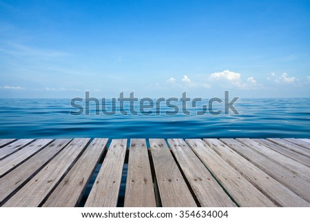 Wooden bridge over beautiful seascape with blue sea, blue sky and cloud background. - stock photo