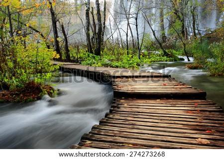 wooden bridge over river - stock photo